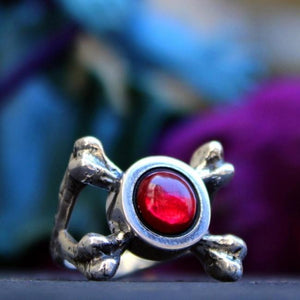 shot of the Skeletor armor Ring on a black stone with a skeletor toy in the background