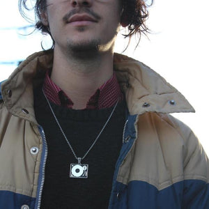 shot of a man in a jacket wearing the turntable pendant in silver