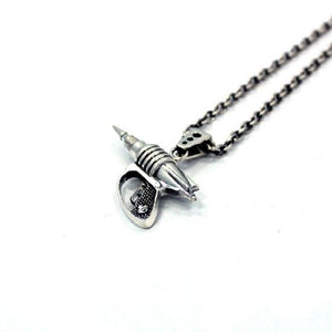 right side shot of the Zap pendant in silver on a white surface