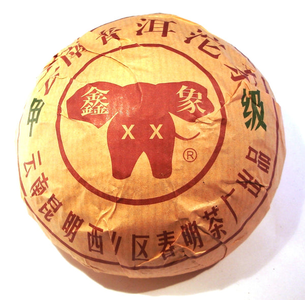 Elephant Xin Xiang Chinese Shou Pu-erh tea tuo in gold packaging with red writing and a red elephant