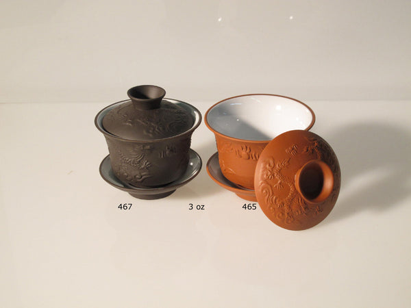 2 yixing clay gai wans with dragon pattern - one is red, the other is brown