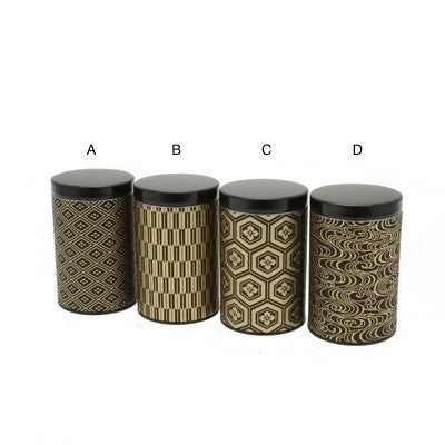 four black and gold tea canisters with different patterns