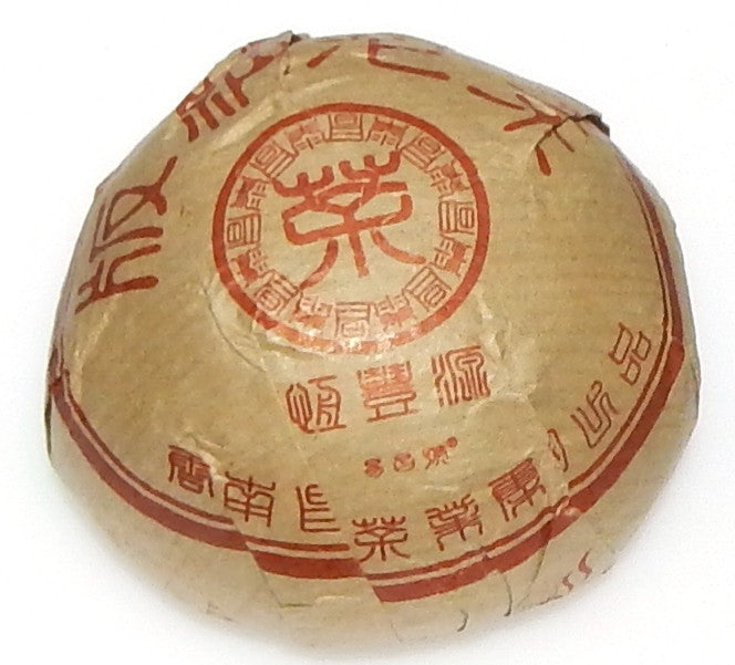 Bana Tuo Shou Pu-erh tea tuo in brown packaging with red characters