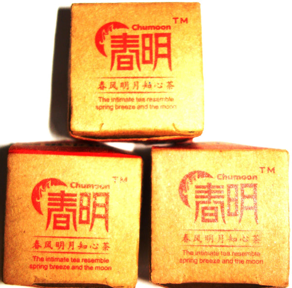 Three bricks of Chun Moon Sheng Pu-ehr tea in gold packaging with red lettering