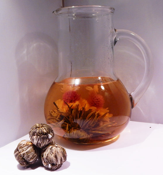 Double Happiness Chinese Green Tea - A pitcher of tea with a blooming tea ball inside and a pile of blooming tea balls to the bottom left