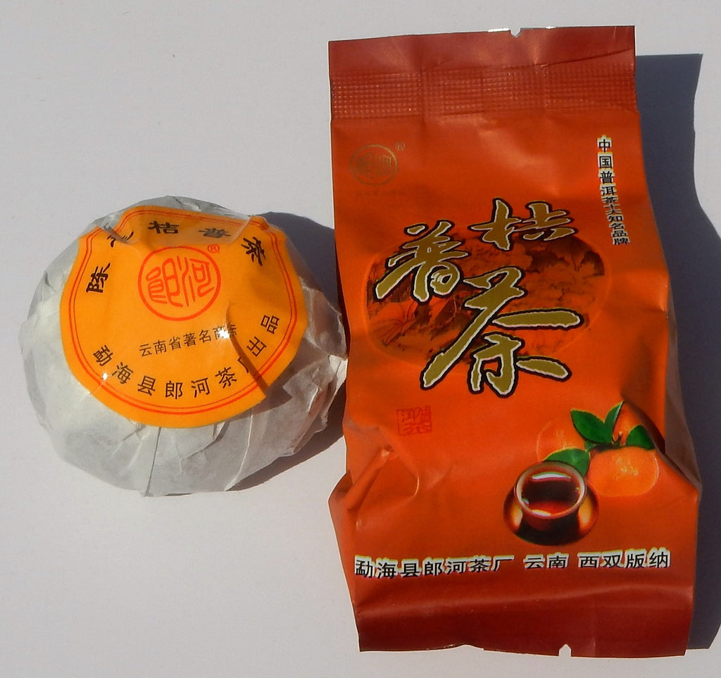Jipu Cha Mandarin Chinese Shou Pu-erh tea tuo wrapped in white packaging with an orange sticker and an orange outer packaging