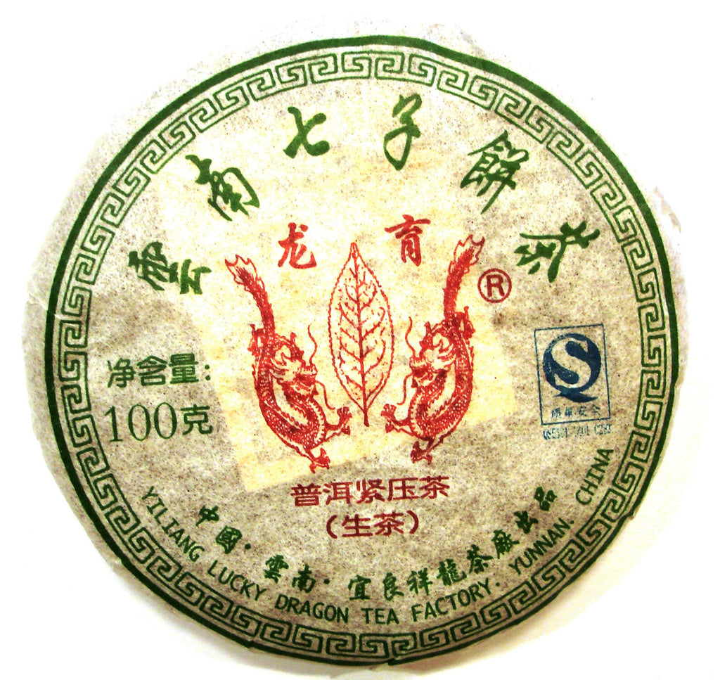 Lucky Dragon Chinese Sheng pu-erh tea cake in white packaging with green characters and red design