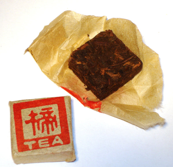 Mini Fangcha Chinese Shou Pu-erh tea brick in an open package, next to a sealed beige package with red characters