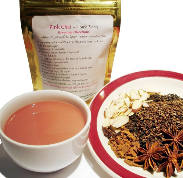 Pink Chai tea blend- loose spices on a dish, a small white cup of steeped tea, Pink Chai blend in gold packaging