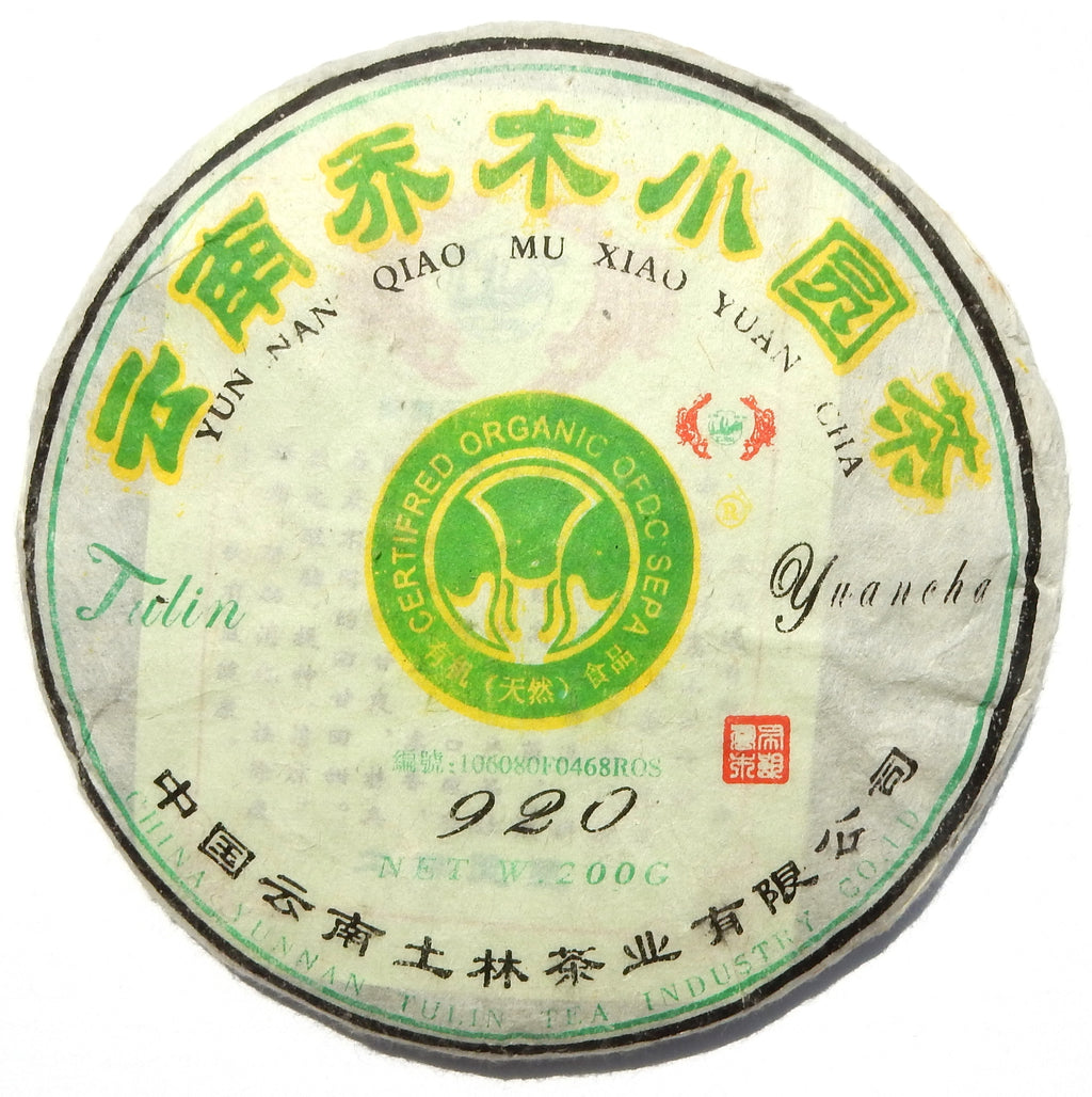 Qiao Mu Chinese Sheng Pu-ehr tea cake in white packaging with bright green and yellow characters