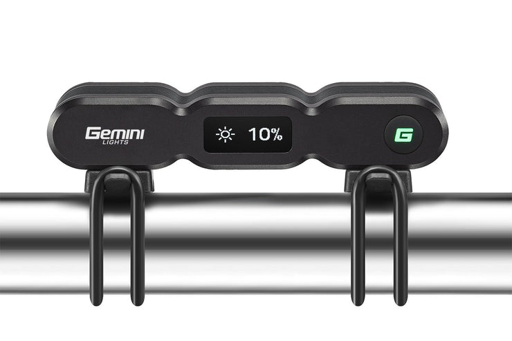 Gemini Titan 4000 OLED bike light mounted on a bicycle handlebar, rear facing displaying 10% brightness on the OLED display