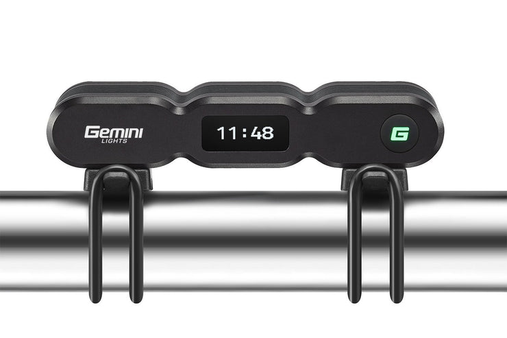 Gemini Titan 2500 OLED bike light mounted on a bicycle handlebar, rear facing displaying runtime remaining on the OLED display