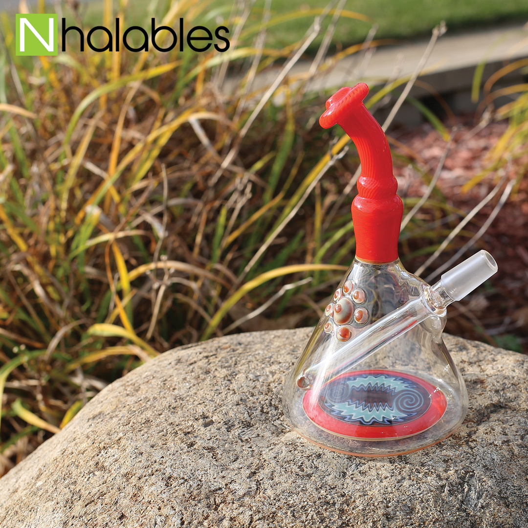Nhalables Social Post showing a orange oil rig by Austin Bray sitting on a rock with some tall grass behind it.