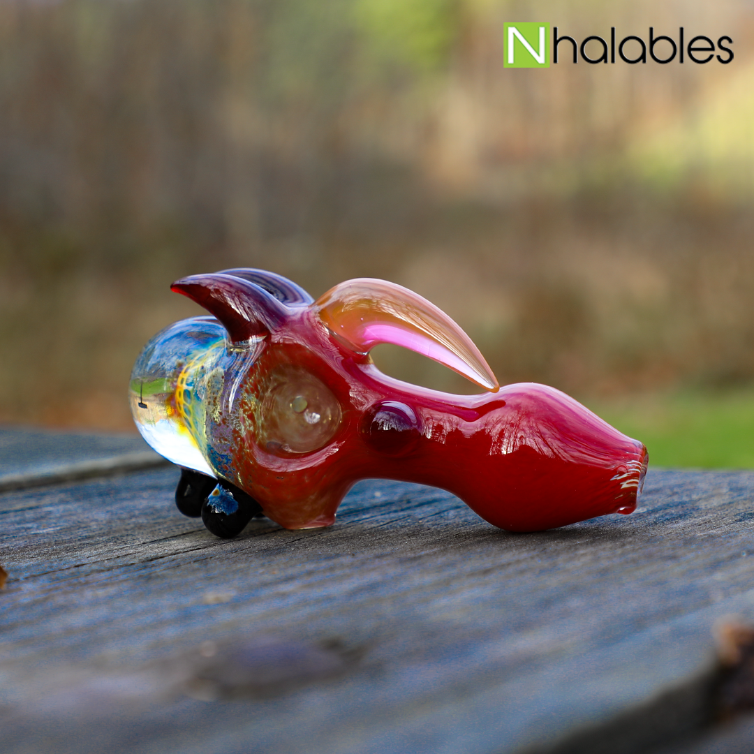 "Nhalables Social image for a Fume Implosion Spoon by Ohio Based ""Catfish Glass"" (Old Country Blew) sitting on a picnic table with trees in the background"