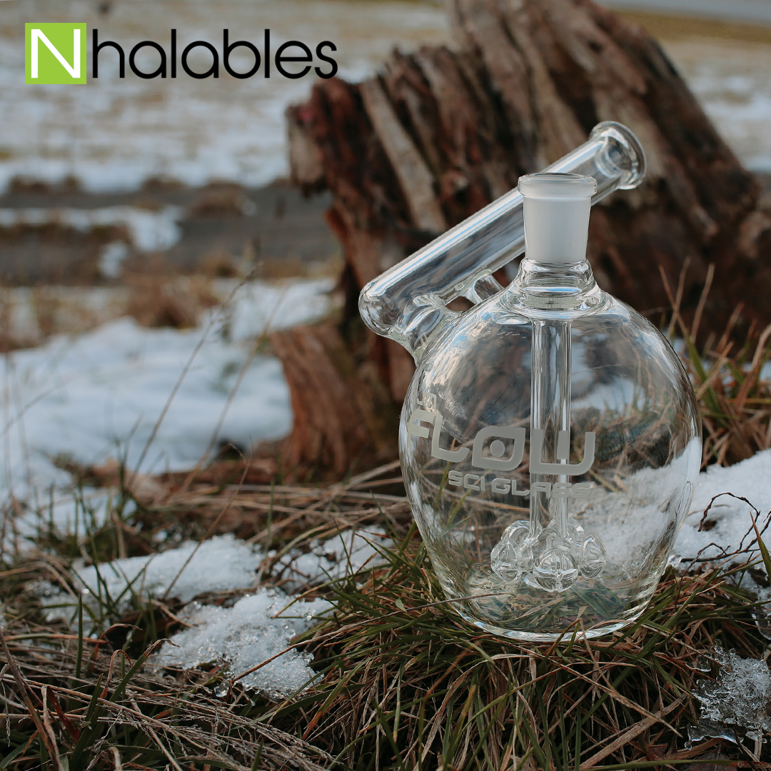 Nhalables Social Post Showing a Jm Flow Apple Rig with a cross percolator sitting on grass in front of a stump.