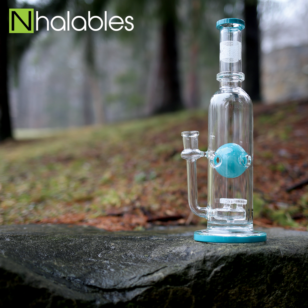 Nhalables Social Post showing a Mav Glass (California) Teal colored Triple Up Ball Waterpipe sitting on a wet rock with leaves, grass, and trees in the background