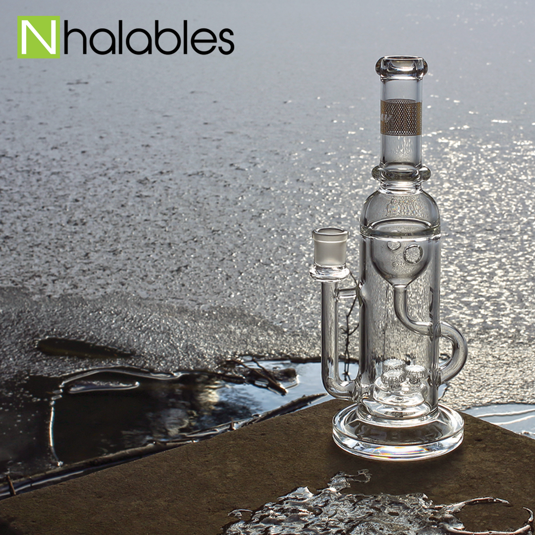 Nhalables Social Post showing a Mav Glass (California) Triple Up Inclycler Waterpipe sitting on a rock in front of a pond at sunset