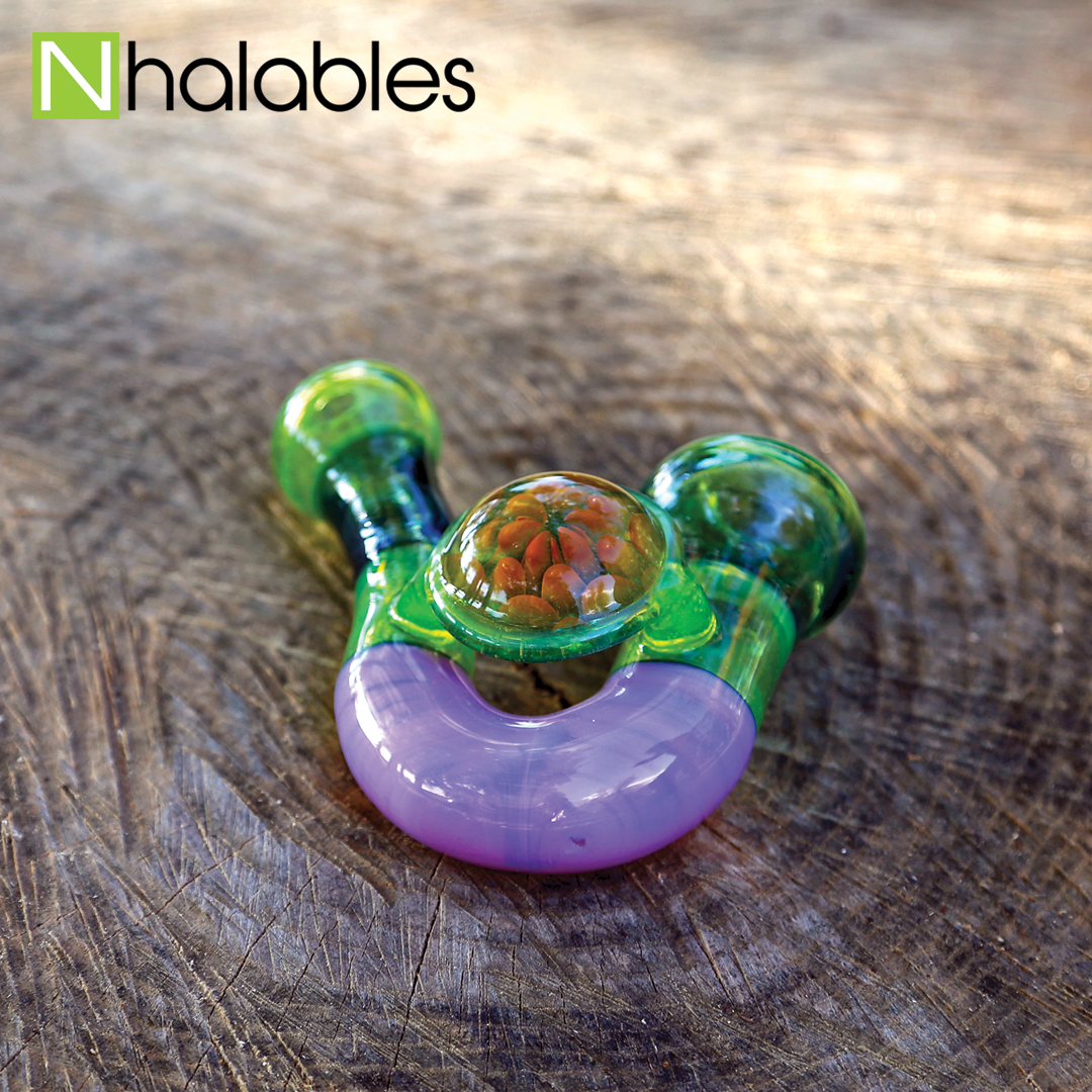 Nhalables Social Post showing a Slyme Green Sherlock Handpipe made by Oregon Rone Glass sitting on a wooden stump.