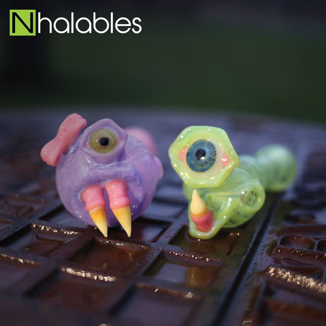 Nhalables Social Post showing two Glass Sculpted Monster Handpipes By cleveland based artist Lacorte Lampworking sitting on a sewer lid at sun down.