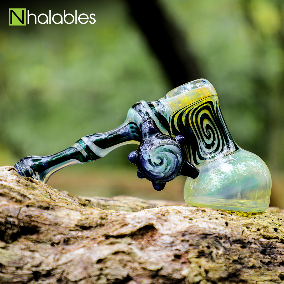 "Nhalables Social Posts of a Worked Hammer Bubbler Water Pipe by Ohio based ""BTS Glass"" sitting on a wooden log"