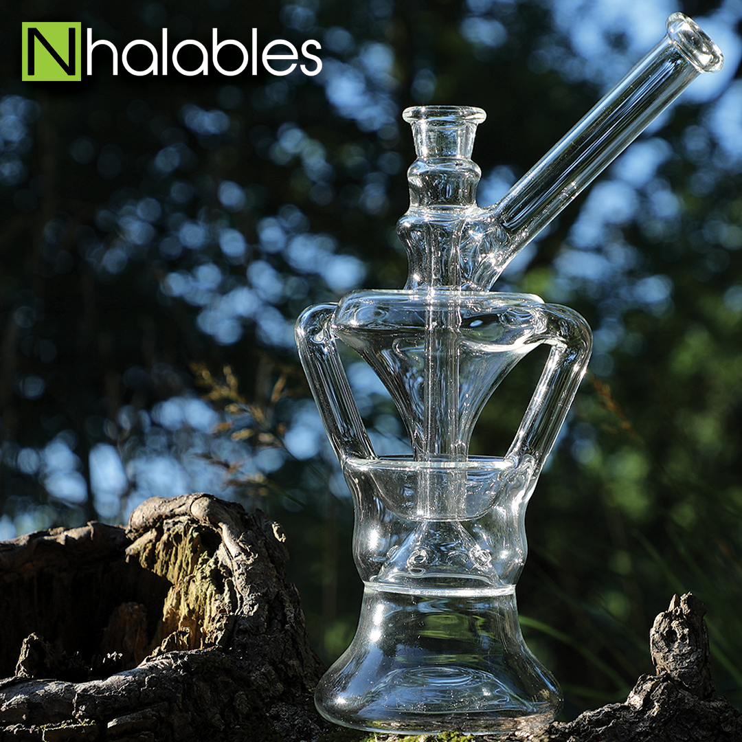 Nhalables Social Post showing a Cleveland Based artist Bronztucky Glass - Centrifuge Recycler sitting on a wooden log with trees in the background