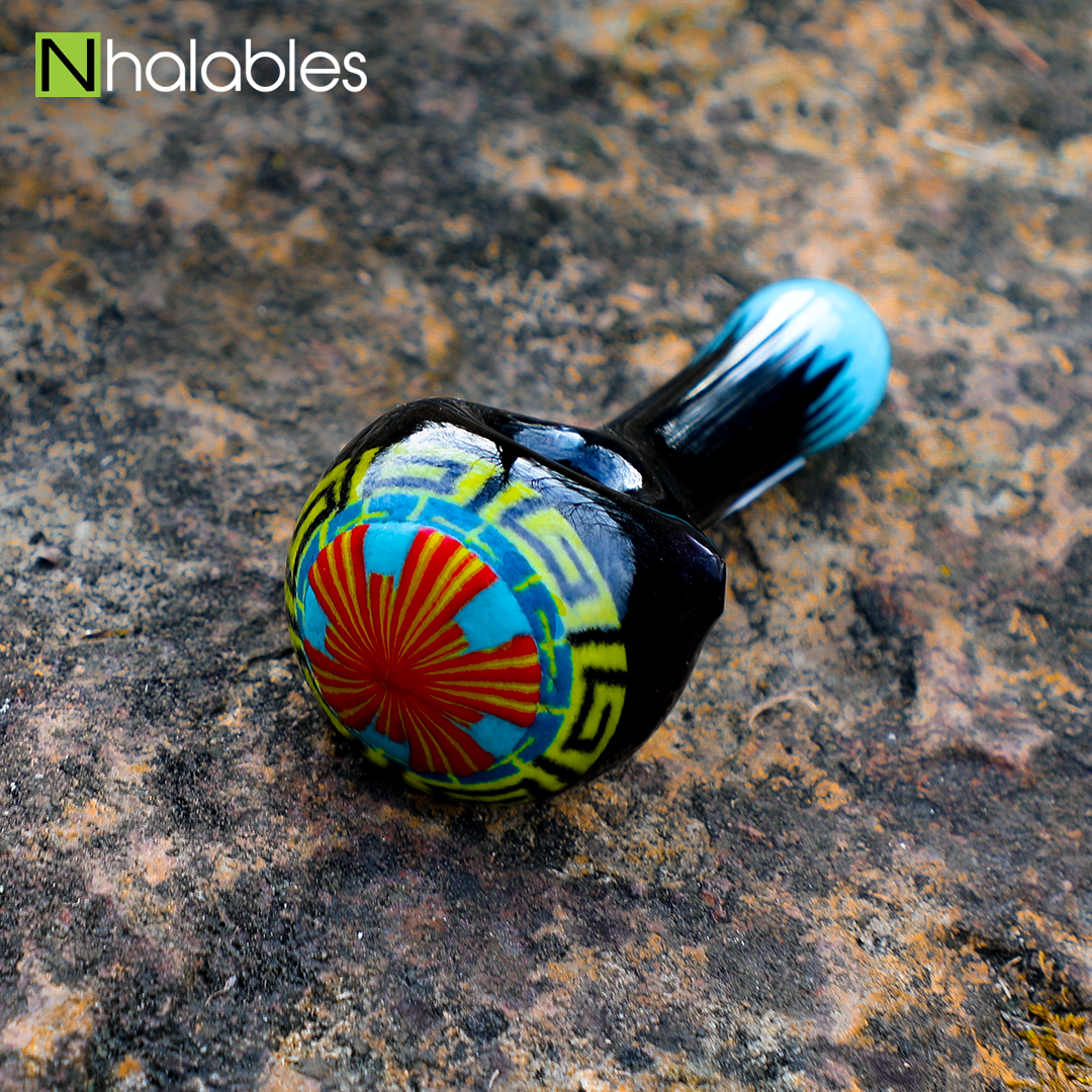 Nhalables Social Image for a Aztec Hand pipe by Michigan Based Glassblower Hoffman Glass sitting on a rock.