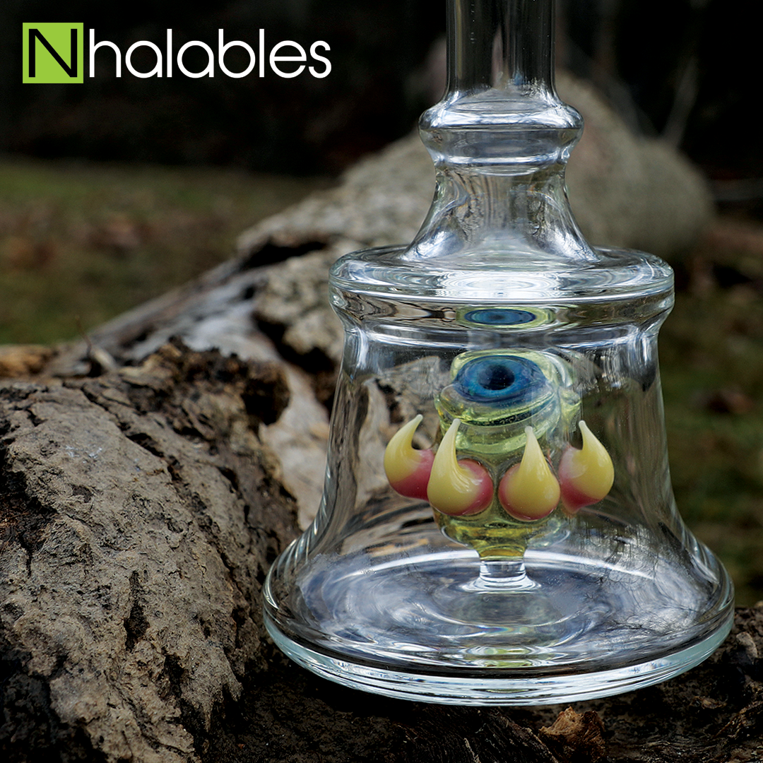 Nhalables Social Post showing a Tony Lacorte from Lacorte Lampworking Bottle Monster Oil Rig sitting on the ground next to a log.