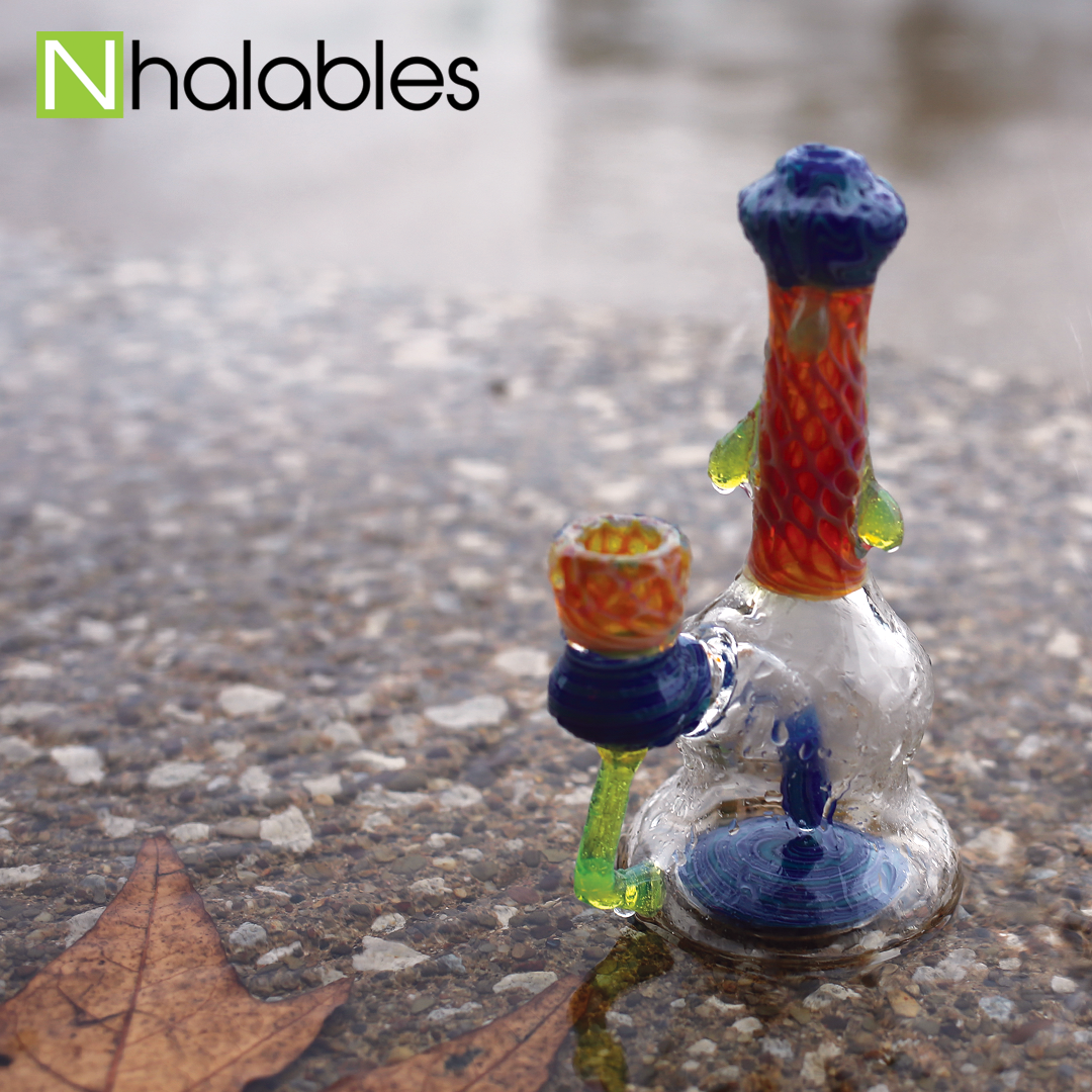 Nhalables Social Post showing Kentucky based artist Plug a Nug honeycomb banger hanger sitting on the asphalt in the rain.