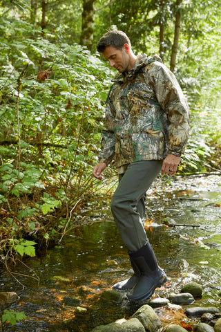 Man wearing mostly camo walking into a river in the forest
