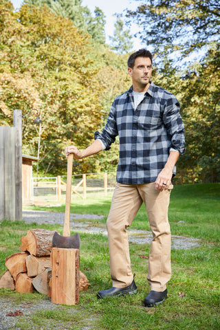 Man standing next to a pile of wood while holding an axe