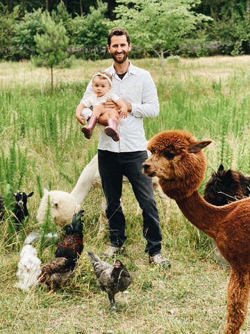 Father holding his daughter near a bunch of alpacas outside