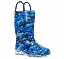 A light up Western Chief rain boot with shark print, clear outsole, and two pull handles.
