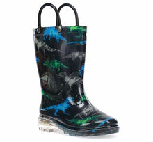 A Western Chief kids rain boot with dinosaur print, light up outsole, and two black pull handles.