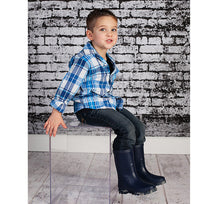 Kid sitting in blue jeans, plaid blue and white shirt, and Youth Camo Sole Solid Rain Boots.