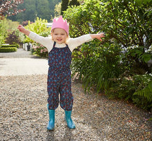 A little girl models her blue glitter rain boots with white t-shirt, pink crown, and red and blue jumpsuit.