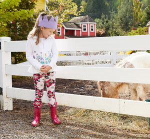Little girl in a fashionable outfit with pink glitter rain boots smiles at a cow on a farm.
