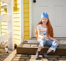 Lifestyle image of girl sitting outside her home modeling the Western Chief Youth Glitter Rain Boots.