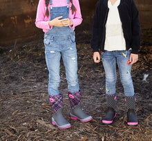 Two kids stand outside in casual outfits and model Western Chief neoprene boots.