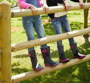 Two kids stand on a fence in casual outfits and printed neoprene boots.