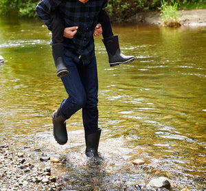 Lifestyle image showing a dad and his son walking in water with Western Chief neoprene boots.