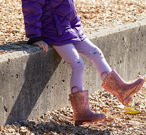 Little girl in purple outfit wears Western Chief signature rose gold glitter rainboots.