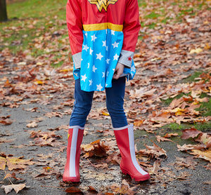 Lifestyle shot of girl wearing Western Chief Wonder Woman Rain Boots for youth and matching coat.