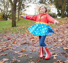 A youth outside on a windy day modeling off her Youth Wonder Woman Rain Boots, matching coat, and denim jeans.