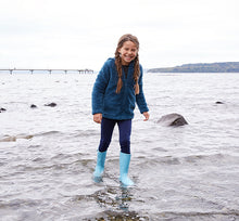 Smiling model wearing a dark blue outfit with light blue Western Chief tall youth rain boots.