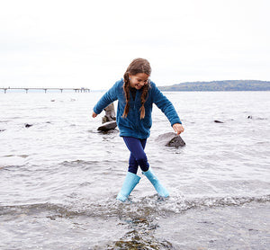 A girl at the beach stomping through the water in a dark blue outfit and kids light blue rain boot.