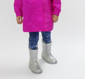 Studio shot of model modeling Western Chief pink rain cat and silver glitter boots.