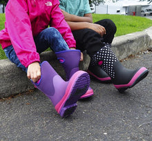 Lifestyle image focusing on kids neoprene boots in purple and dot print.