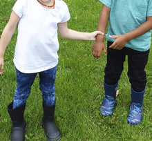 Two children stand outside in grass and model our black neoprene boot and printed neoprene boots.