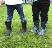 Lifestyle image showing two children outside modeling for Western Chief printed and solid neoprene boots.