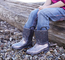 Lifestyle shot of girl on log with focus on her multi-color glitter rain boots.